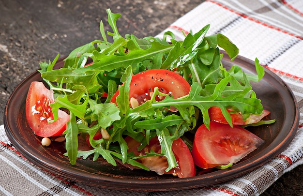 Salad with arugula, tomatoes and pine nuts