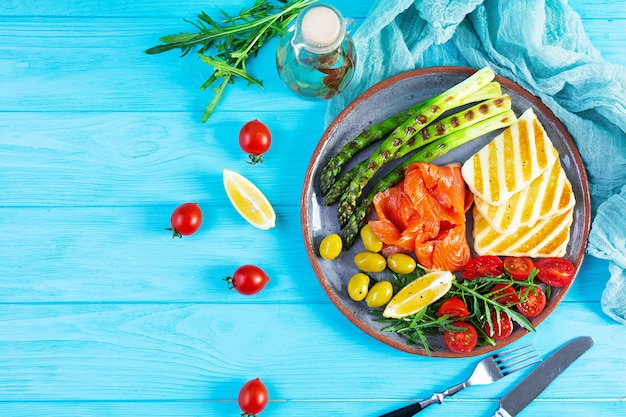 Salad with asparagus, grilled halloumi cheese, salmon fillet, tomatoes, arugula and green olives. top view