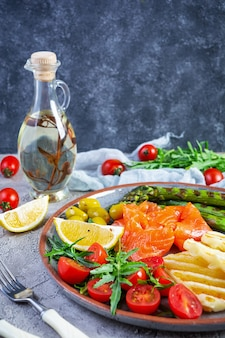 Salad with asparagus, grilled halloumi cheese, salmon fillet, tomatoes, arugula and green olives