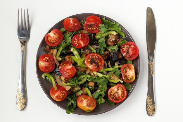 白い表面の暗いプレートに茄子とチェリートマトのサラダ、上面図、テーブルの上にナイフとフォークがあります