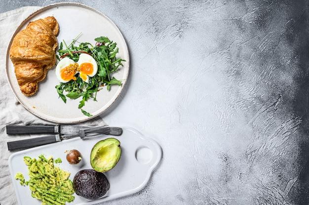 Салат с авокадо, рукколой, круассаном и яйцом. серый фон вид сверху. пространство для текста