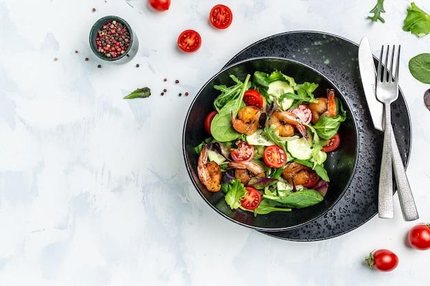 Салат с авокадо и креветками в миске, вкусный завтрак или закуска на светлом фоне, вид сверху.