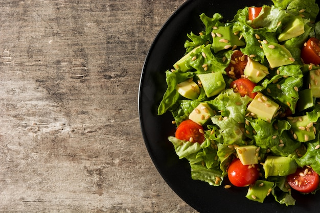 Salad with avocado, lettuce, tomato, flax seeds on wooden table copy space