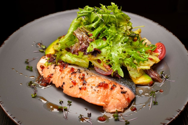 Salad with avocado and salmon, on a black background