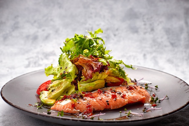 Salad with avocado and salmon, on a light background