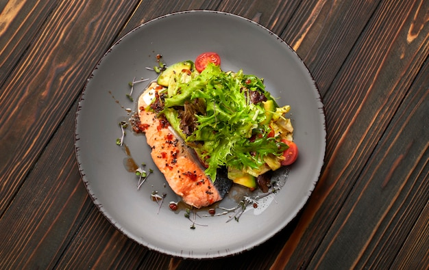 Salad with avocado and salmon, on a wooden background