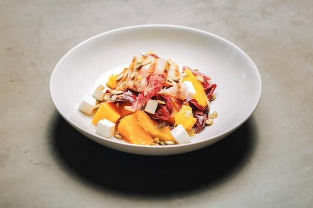 Салат с беконом. вид сверху на здоровый питательный салат с беконом и сыром фета, стоящий на столе