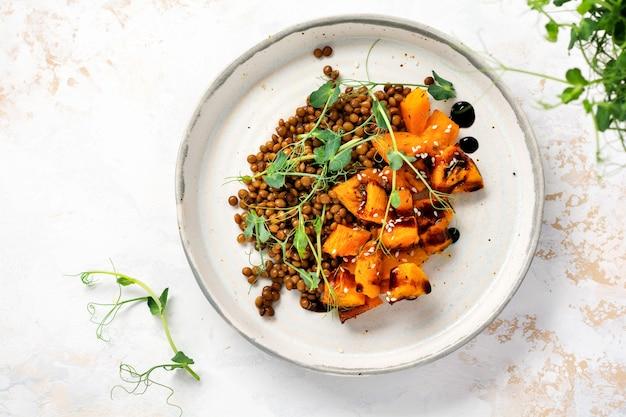 구운 호박, 렌즈콩, 발사믹 드레싱을 곁들인 샐러드와 밝은 배경에 완두콩 마이크로그린으로 장식되어 있습니다. 건강한 채식주의 음식, 최고 전망