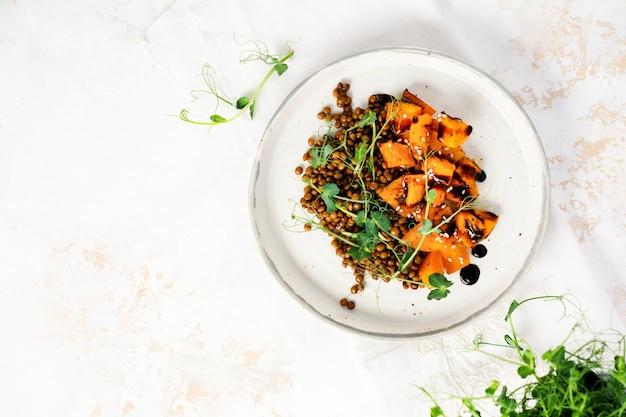 焼きカボチャ、レンズ豆、バルサミコドレッシングのサラダにエンドウ豆のマイクログリーンを添えてライトで