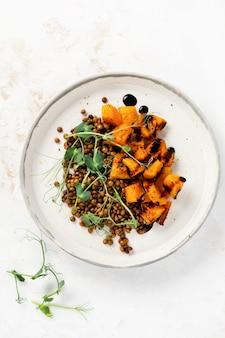焼きカボチャ、レンズ豆、バルサミコドレッシングのサラダにエンドウ豆のマイクログリーンを添えて