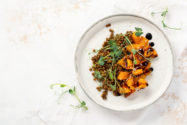 Salad with baked pumpkin, lentils and balsamic dressing garnished with peas microgreens on a light