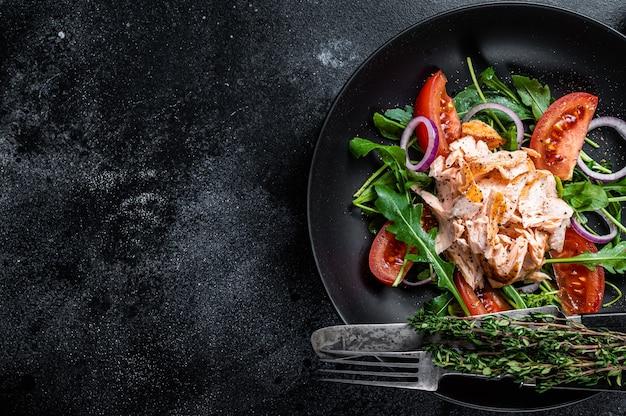 구운 연어 필레 스테이크, 신선한 아루 굴라, 토마토를 접시에 담은 샐러드
