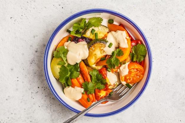 白い背景に、上面に白い皿にタヒニと焼き野菜のサラダ。きれいな食事のコンセプト。