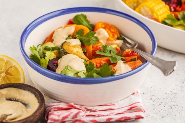 白いプレート、白い背景でタヒニと焼き野菜のサラダ。きれいな食事のコンセプトです。