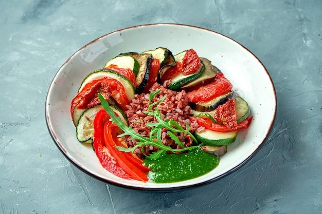 회색 배경에 흰색 그릇에 구운 호박, 토마토, 고추, 가지, 야생 쌀 샐러드