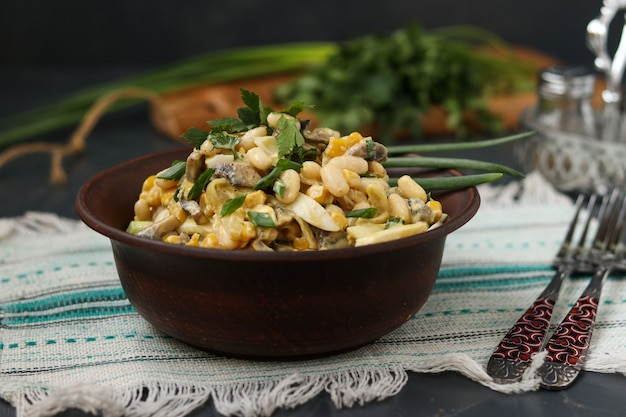 Salad with beans, corn, eggs and champignons in a brown bowl