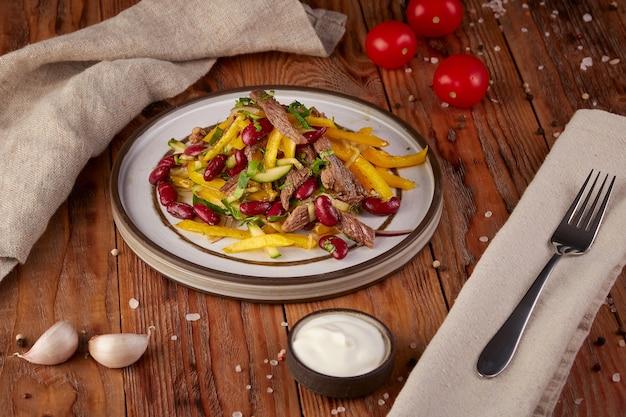 Салат с фасолью, мясом, перцем и огурцом, деревянный фон
