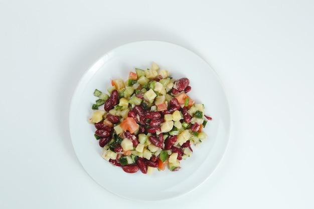 콩, 토마토, 양파, 감자 근접 촬영 하얀 접시에 샐러드. 콩 샐러드 고립 된 상위 뷰