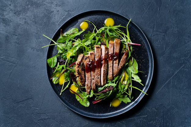 Salad with beef tenderloin, arugula and chard on a black plate.