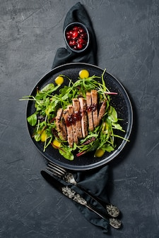 Salad with beef tenderloin steak, arugula and chard on a black plate.