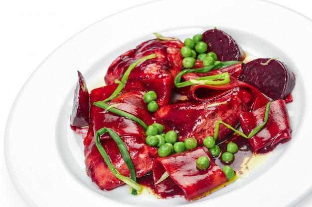 Salad with beets, peas and meat isolated on white