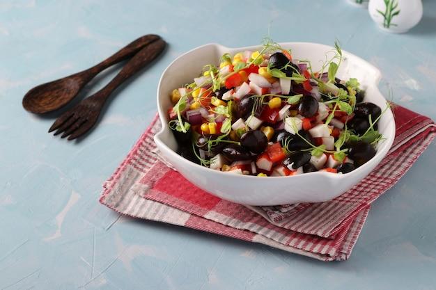 Салат с черной фасолью, кукурузой, крабовыми палочками и микрогринами из гороха в белой миске на голубой поверхности, горизонтальный формат