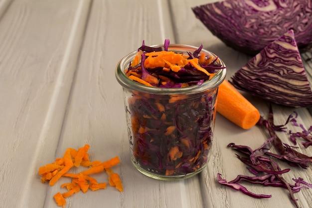 Салат с голубой капустой и морковью в стеклянной банке на сером деревянном фоне