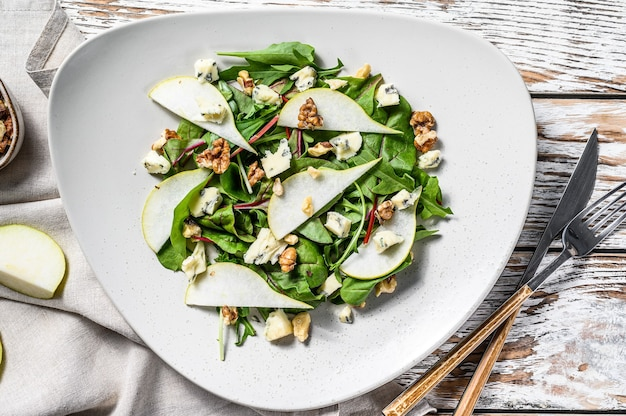 Salad with blue cheese, pears, nuts, chard and arugula. white background. top view.