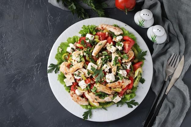 暗い表面の白いプレートにブルガー、焼きチキン、ピーマン、バジル、フェタチーズのサラダ。上からの眺め。水平フォーマット