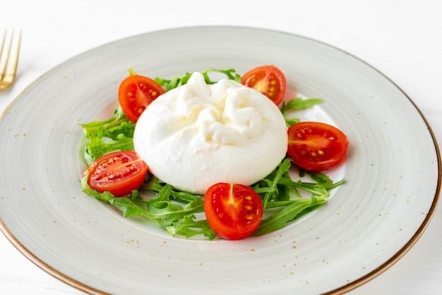 白い木製の背景にブッラータ チーズとミニトマトのサラダ