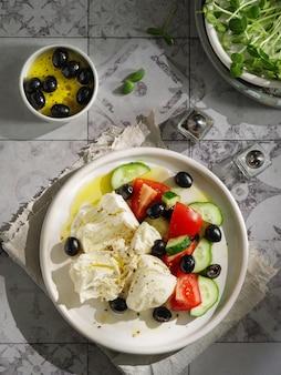 부라타 치즈, 오이, 블랙 올리브, 토마토를 곁들인 샐러드가 그릇에 제공됩니다. 부라타 치즈를 곁들인 건강한 채식 저녁 식사.