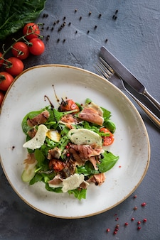 Salad with burrata, parma and cherry tomatoes confit