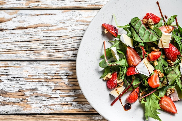 Salad with camembert, strawberries, nuts, chard and arugula. white background. top view. copy space.