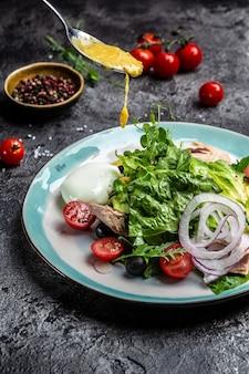 Салат с консервированным тунцом, авокадо, пашот, яйцом, листьями салата, черри, томатами, оливками и кукурузой.