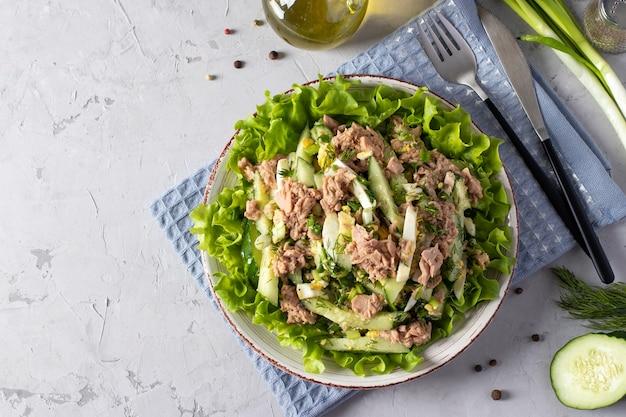 Салат с консервированным тунцом, зеленым луком, яйцом и огурцом, заправленный оливковым маслом. подается на зеленых листьях салата. здоровая пища. вид сверху