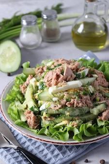 참치 통조림, 파, 계란, 오이를 올리브 오일로 맛을 낸 샐러드. 녹색 양상추 잎에 제공됩니다. 건강한 음식. 세로 형식