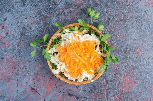 나무 접시에 당근, 양배추, 허브를 넣은 샐러드.