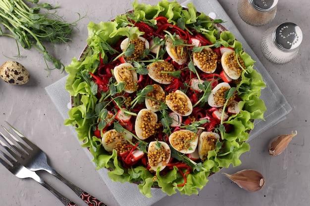 밝은 회색 배경에 겨자와 올리브 오일로 양념한 당근, 비트 뿌리, 유기농 상추 잎, 완두콩 마이크로그린, 메추라기 알을 곁들인 샐러드