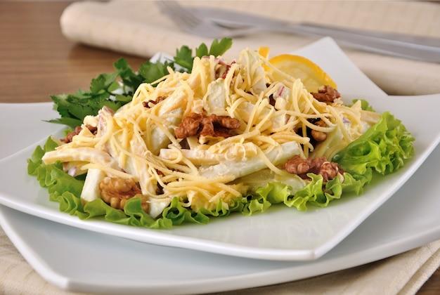 Салат с сыром и яблоками грецкими орехами и йогуртом на листьях салата с лимоном