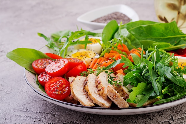 Salad with cherry tomatoes, chicken breast, eggs, carrot, arugula and spinach