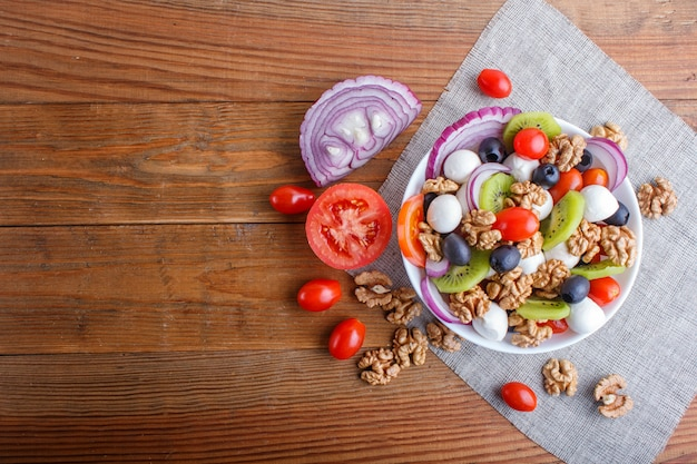 Salad with cherry tomatoes, mozzarella cheese, olives, kiwi, and walnuts on brown wooden background.