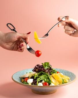 Салат с помидорами черри моцарелла кукуруза руккола апельсин и яблоко на тарелке