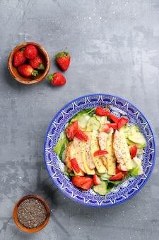 닭고기와 딸기, 망고 및 치아 씨앗 상위 뷰 샐러드. 콘크리트 테이블에 고기와 과일 샐러드.