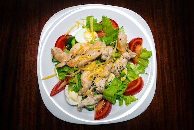 白い皿に鶏肉と野菜のサラダ