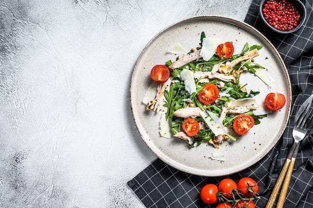 Салат с курицей, рукколой, грецкими орехами, помидорами и пармезаном. серый фон