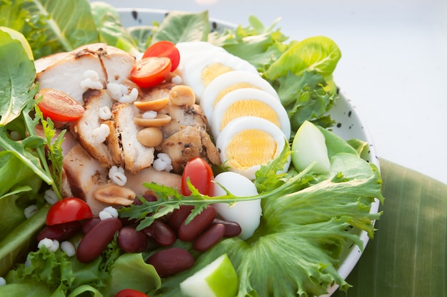 Salad with chicken breast and boiled egg, close up healthy food