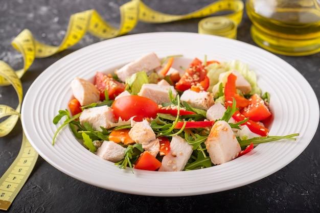 チキン、チェリートマト、赤唐辛子、ルッコラのサラダ。ダイエットのコンセプト。閉じる