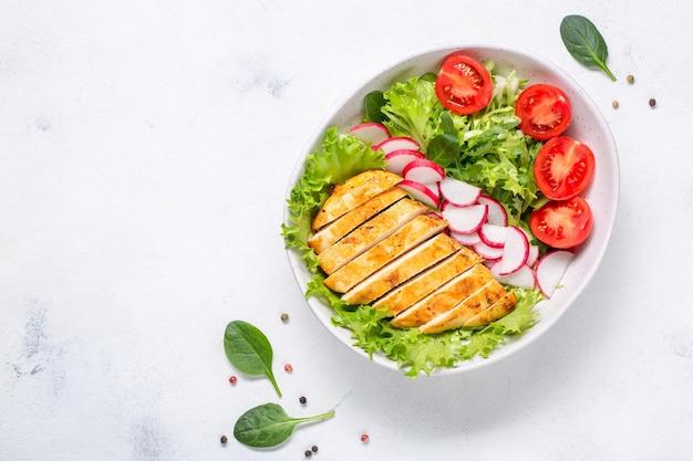 鶏の切り身のサラダ。ケトダイエット、健康食品、ダイエットランチ。白い背景の上面図。