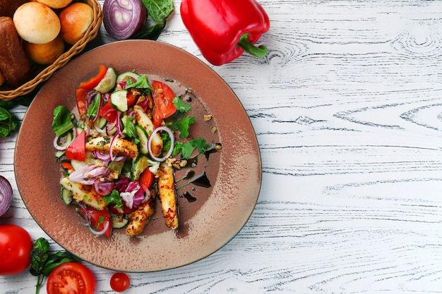 Салат с курицей в тарелке и овощными ингредиентами на деревянном столе.