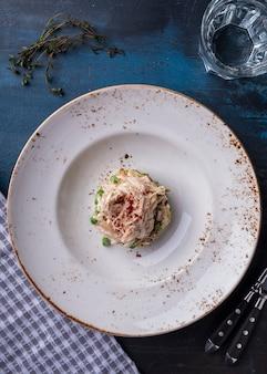 Салат с курицей, грибами, луком, зеленым горошком, огурцом и яйцом. вид сверху